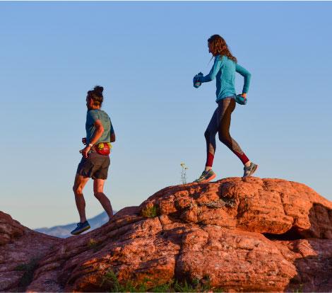 Runners trekking over red rocks.
